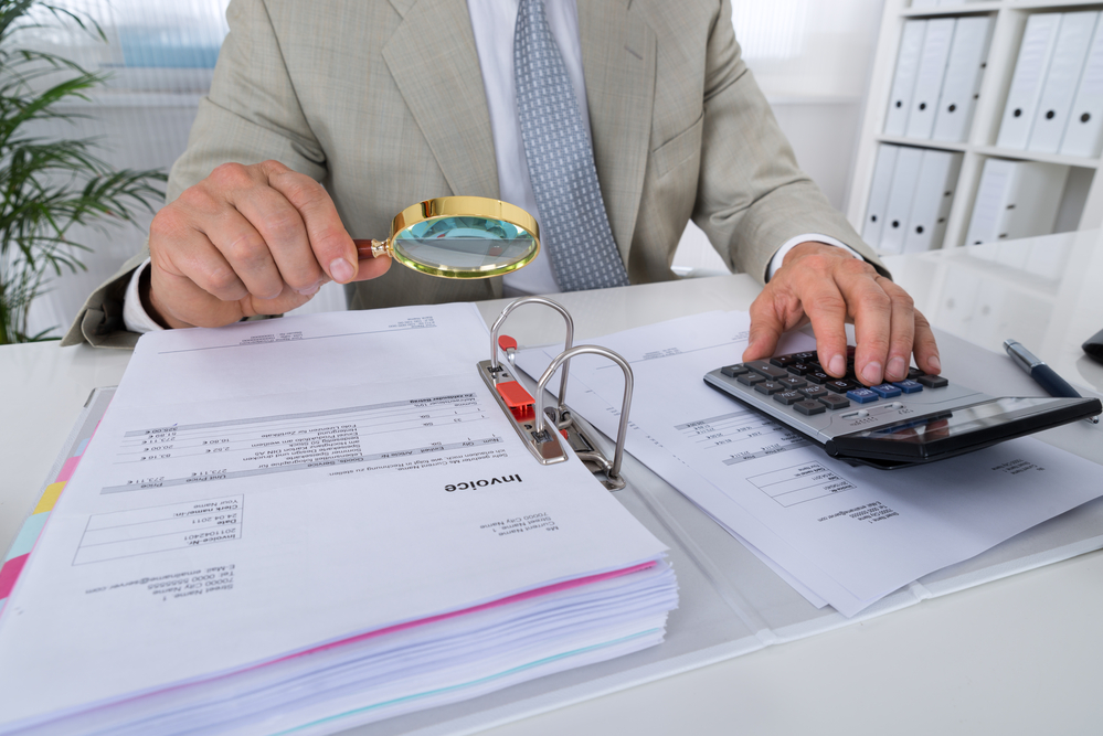 A man holding a magnifying glass over an invoice while using a calculator