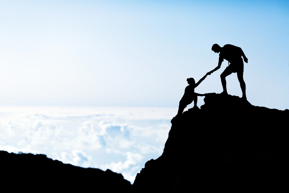 An individual helping another person reach the top of a mountain