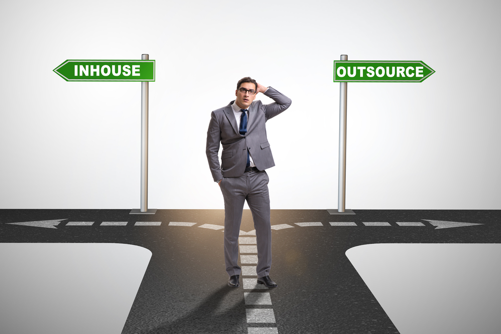 A man choosing between the outsourcing road or the in-house road